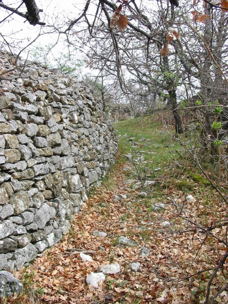 Une rue longeant un mur du hameau.